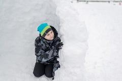 Muchacho adolescente que se sienta en fuerte hecho en casa de la nieve Fotos de archivo