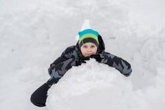 Muchacho adolescente que se sienta en fuerte hecho en casa de la nieve Imagen de archivo