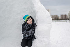Muchacho adolescente que se sienta en fuerte hecho en casa de la nieve Imagenes de archivo