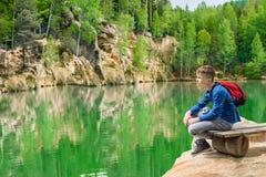 Muchacho adolescente que se sienta en la orilla del lago Piskovna Imagen de archivo