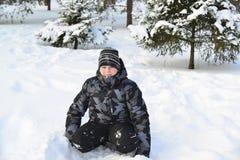 Muchacho adolescente que se sienta en nieve en el bosque del invierno Imágenes de archivo libres de regalías