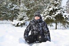 Muchacho adolescente que se sienta en nieve en el bosque del invierno Fotografía de archivo
