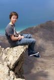 Muchacho adolescente que se sienta en una roca en la costa Imágenes de archivo libres de regalías