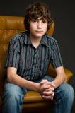 Muchacho adolescente que se sienta en una silla Imagen de archivo libre de regalías