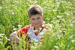 Muchacho adolescente que se sienta entre las flores del prado Foto de archivo libre de regalías