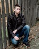 Muchacho adolescente que se sienta por la cerca de madera Fotos de archivo libres de regalías