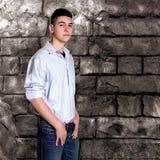 Muchacho adolescente que se sienta por la pared de piedra Imágenes de archivo libres de regalías