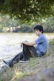 Muchacho adolescente que se sienta por Lake Imágenes de archivo libres de regalías