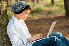 Muchacho adolescente que socializa en el ordenador portátil al aire libre. Fotos de archivo libres de regalías