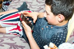 Muchacho adolescente que sostiene smartphone y que juega a los juegos que ponen en el sofá Imagenes de archivo