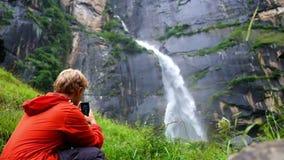 Muchacho adolescente que tira la cascada famosa de Jogini con su smartphone en Manali, la India metrajes
