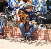 Muchacho adolescente que toca el instrumento en gafas de sol en el festi Foto de archivo libre de regalías