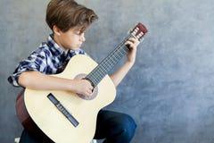 Muchacho adolescente que toca la guitarra acústica Foto de archivo libre de regalías