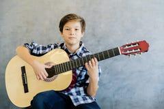 Muchacho adolescente que toca la guitarra acústica Fotografía de archivo libre de regalías