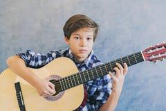 Muchacho adolescente que toca la guitarra acústica Foto de archivo