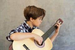 Muchacho adolescente que toca la guitarra acústica Fotos de archivo libres de regalías