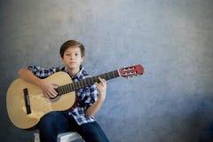Muchacho adolescente que toca la guitarra acústica Imagen de archivo