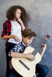 Muchacho adolescente que toca la guitarra acústica mientras que muchacha adolescente que escucha él Foto de archivo