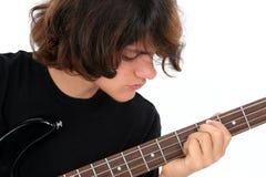 Muchacho adolescente que toca la guitarra baja imagenes de archivo