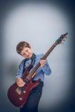 Muchacho adolescente que toca la guitarra en cruz gris del fondo Foto de archivo libre de regalías
