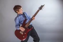 Muchacho adolescente que toca la guitarra en fondo gris Imagenes de archivo