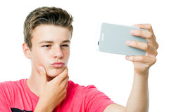 Muchacho adolescente que toma el autorretrato con el teléfono elegante Fotos de archivo