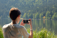 Muchacho adolescente que toma la imagen con smartphone fotografía de archivo