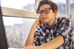 Muchacho adolescente que usa el ordenador portátil por la ventana Fotos de archivo libres de regalías