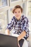 Muchacho adolescente que usa el ordenador portátil por la ventana Foto de archivo