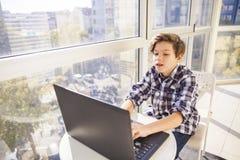 Muchacho adolescente que usa el ordenador portátil por la ventana Imagen de archivo