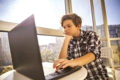 Muchacho adolescente que usa el ordenador portátil por la ventana Foto de archivo libre de regalías