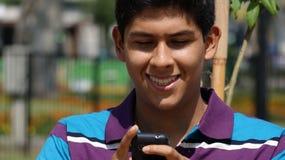 Muchacho adolescente que usa Smartphone Fotografía de archivo