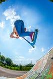 Muchacho adolescente que va aerotransportado con una vespa Foto de archivo