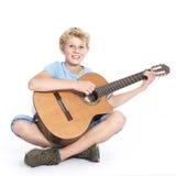 Muchacho adolescente rubio con la guitarra en estudio contra el fondo blanco Imagen de archivo
