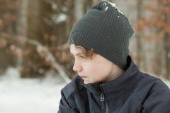 Muchacho adolescente serio en Gray Hat Outdoors en invierno Imagen de archivo libre de regalías