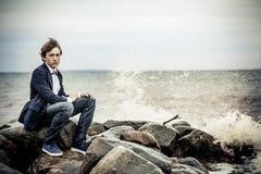 Muchacho adolescente serio que se sienta en rocas en la playa Imagen de archivo