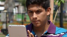 Muchacho adolescente serio que usa la tableta Foto de archivo