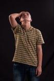 Muchacho adolescente serio y pensativo con la mano en la cabeza Foto de archivo libre de regalías