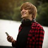 Muchacho adolescente sonriente con el auricular Foto de archivo libre de regalías