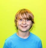 Muchacho adolescente sonriente con el pelo rubio largo Imagenes de archivo