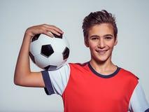 Muchacho adolescente sonriente en la ropa de deportes que sostiene el balón de fútbol Fotografía de archivo libre de regalías