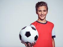 Muchacho adolescente sonriente en la ropa de deportes que sostiene el balón de fútbol Imagen de archivo