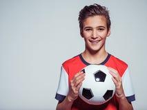 Muchacho adolescente sonriente en la ropa de deportes que sostiene el balón de fútbol Imagen de archivo libre de regalías
