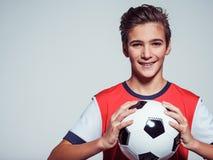 Muchacho adolescente sonriente en la ropa de deportes que sostiene el balón de fútbol Foto de archivo