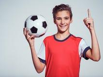 Muchacho adolescente sonriente en la ropa de deportes que sostiene el balón de fútbol Fotos de archivo