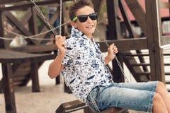 Muchacho adolescente sonriente feliz en gafas de sol en un oscilación Fotografía de archivo