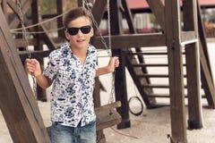 Muchacho adolescente sonriente feliz en gafas de sol en un oscilación Imagen de archivo libre de regalías