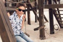 Muchacho adolescente sonriente feliz en gafas de sol en un oscilación Imágenes de archivo libres de regalías