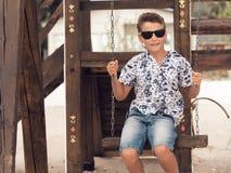 Muchacho adolescente sonriente feliz en gafas de sol en un oscilación Fotos de archivo