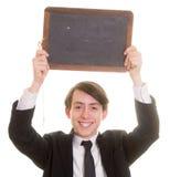 Muchacho adolescente sonriente feliz que sostiene una pizarra en blanco Imagenes de archivo